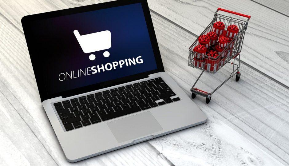 Отворен лаптоп със надпис online shopping вдясно и пазарска количка пълна с подаръци вляво и